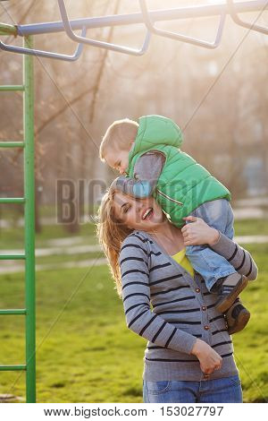Mum takes son to the horizontal bars in the autumn park. Family time. Happiness of childhood and parenthood. Outdoor Activities.