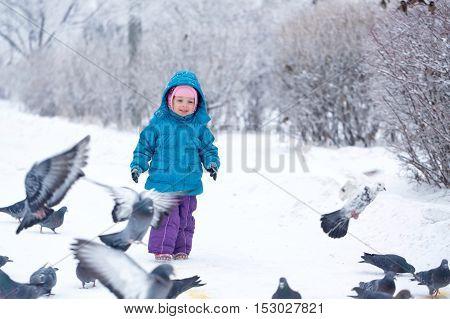 Little girl on a walk in a winter park. Kid frightens pigeons. Childhood Joy.