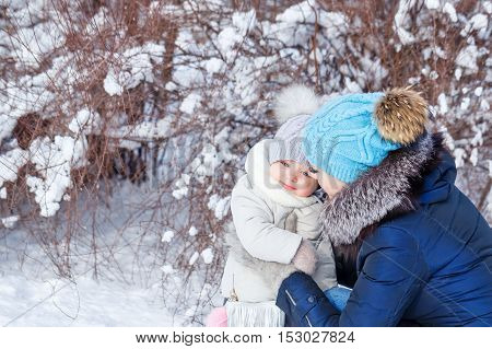 Mother and young daughter embracing in a winter park. Family time. Childhood and parenthood happiness. Close portrait.