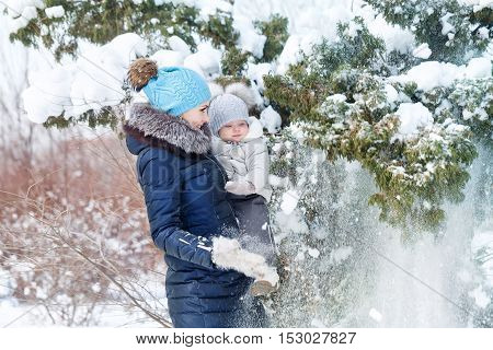 Mother and young daughter embracing in a winter park. Mother and daughter with snow downed trees. Happy family. Childhood and parenthood happiness. Close portrait.