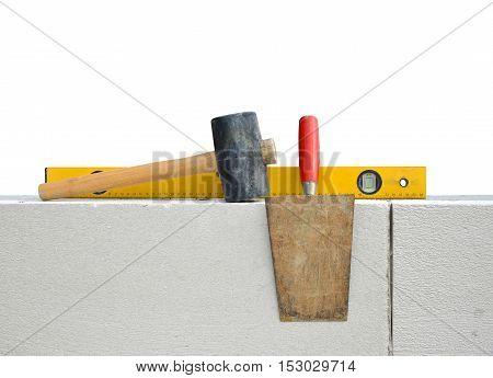 Masonry tools on white wall. Bricklaying work.