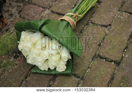 White sympathy roses in a small bouquet on the pavement