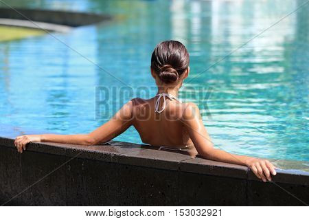 Swimming pool spa retreat relaxation. Relaxing woman lying from the back on infinity edge enjoying sun and serenity in summer holiday travel vacation at resort hotel. Unrecognizable people holidays.