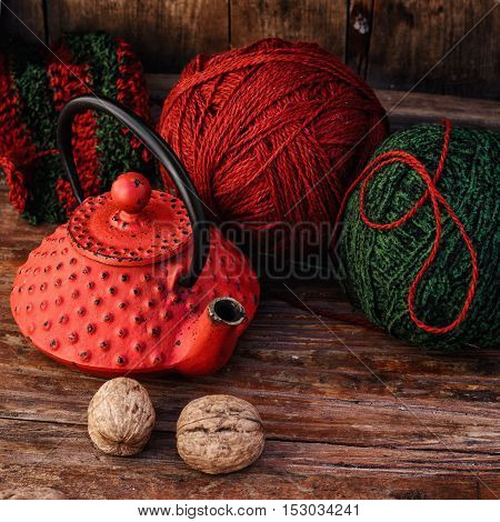 Stylish teapot with warm tea and balls of wool to knit
