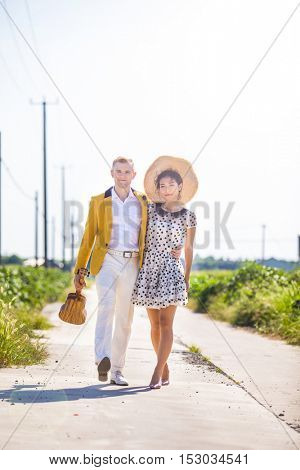 Beautiful multi racial inter racial couple dressed stylishly walking down a an empty road in the countryside