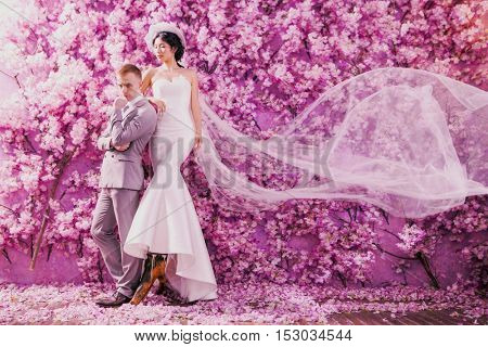 Full length of wedding couple standing against wall covered with pink flowers