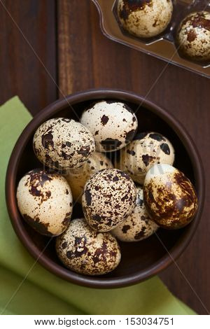Fresh raw quail eggs in rustic bowl photographed overhead with natural light (Selective Focus Focus on the top of the eggs on the top)