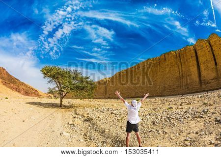 Stone desert near the seaside resort of Eilat. The tourist in a white t-shirt is delighted with desert