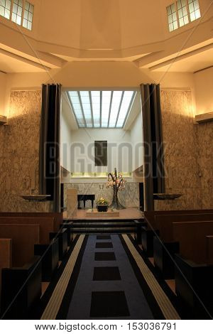Wooden casket with funeral flowers in a crematorium hall
