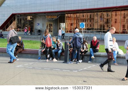 Minsk, Belarus - August 17, 2016: Unidentified young men and women (boys and girls) smoke outside in a specially-designated area for smoking near the railway station. Sunny summer day.