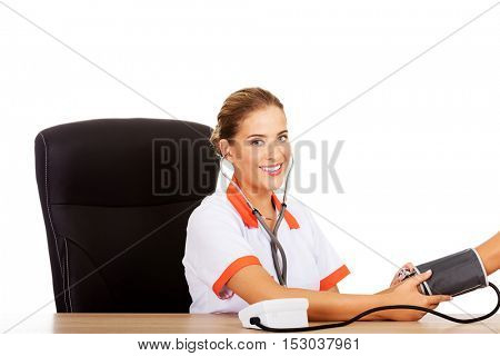 Smile female doctor or nurse checking blood pressure patient