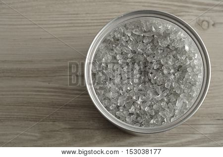 An open tin filled with Grey glass sand top view