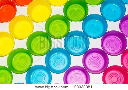 Differently colored colorful glasses on a white background. Taken from above.