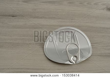A tin lid isolated on a wooden table