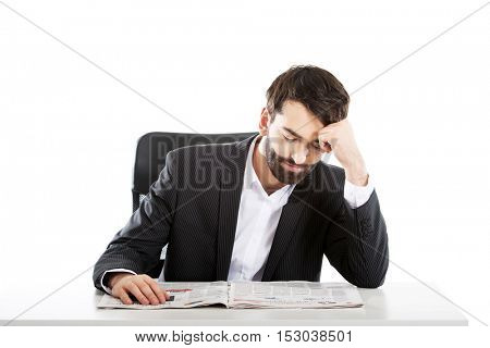 Young man reading newspaper in the office.