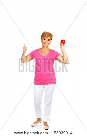Old smiling woman holding red toy heart with thumb up
