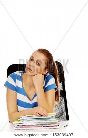Teenage woman sitting behind the desk and thinking