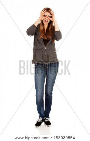 Teenage woman making binoculars hands