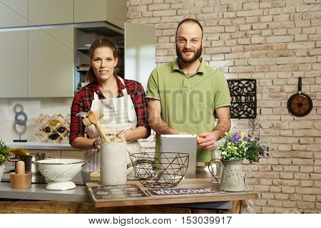 Couple cooking together in kitchen, looking at camera.