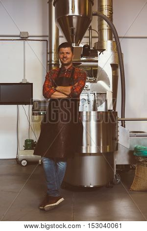 Portrait of smiling handsome worker in apron looking at camera at iron machine