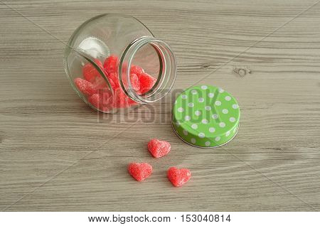 A glass jar with a green polka dot lid half filled with heart shade candy