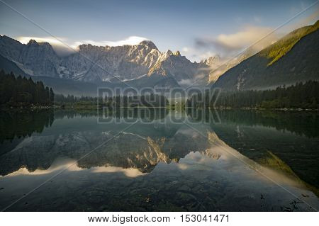 reflection of  mountain Mangart in a mountain lake Laghi di Fusine at sunrise, Julian Alps, Italy
