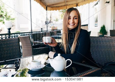 Young beautiful girl smiling and drinking tea in street outdoor cafe. Urban morning scene.
