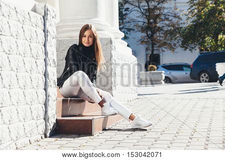 Fashion beautiful girl walking in the city street in autumn. Urban morning scene.