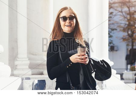 Fashion beautiful girl walking in the city and drinking take away tea by the street outdoor cafe. Urban morning scene.