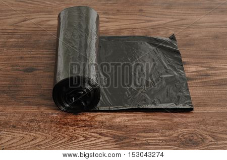 Roll of black garbage bags isolated n a wooden background