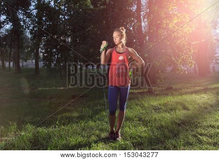 Sporty woman performing exercises using expander in the city park on the green grass