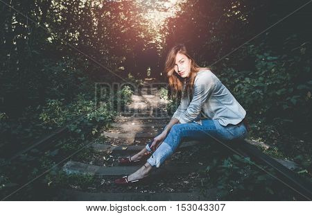 Beautiful woman sitting on the rails and looking straight at you