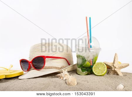 Summer cocktail with beach supplies in the sand on a white background