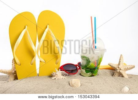 Summer cocktail with beach supplies in the sand on a white background. Summer background