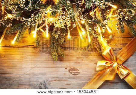 Christmas Background. Christmas holiday fir tree with decoration on dark wooden board background. Border art design with Christmas tree, baubles, light garland and golden gift ribbon with bow