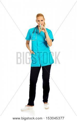 Female nurse or doctor with stethoscope holding syringe