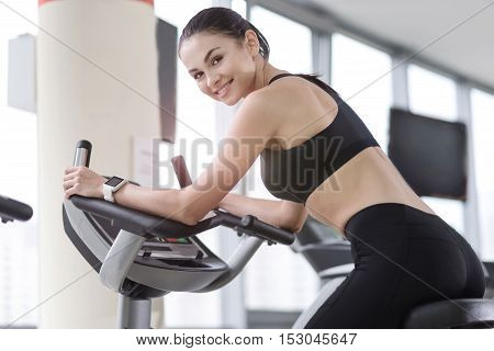 Activity is my passion. Smiling young happy girl using a treadmill while working in a gym and improving her body