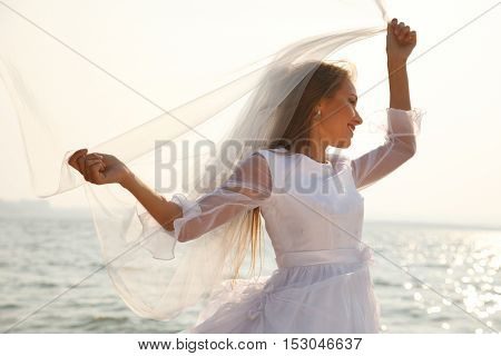 Cheerful bride near sparkling water holding her flying veil