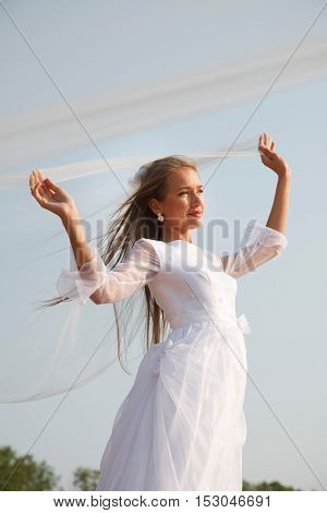 Young bride is holding her flying veil