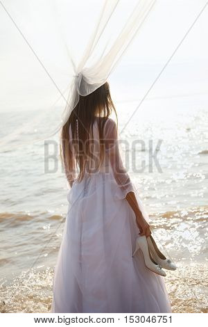 Bride is standing on the beach and holding her shoes