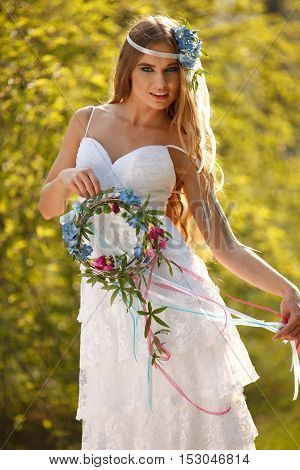 Bride dressed in hippie style stands outdoors in the spring park