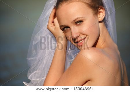 Bride near water line. Close up portrait outdoors
