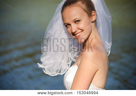 Smiling classical bride  with veil near waterline outdoors