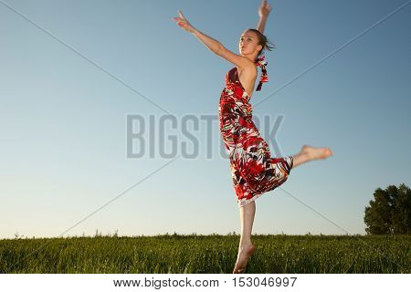 Girl is jumping over the field outdoors