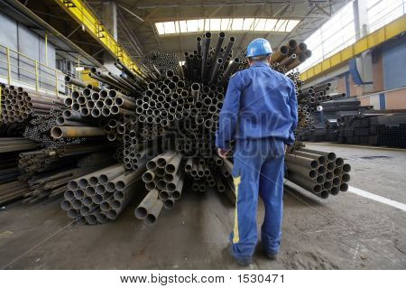 Worker In A Warehouse With Stacks Of Steel Pipes