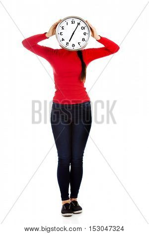 Woman covering face with a clock