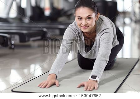 Relaxation moves. Delighted pretty young girl stretching her spine after doing exercises while spending time in a gym.