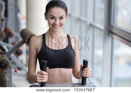 My passion is sport. Joyful pretty delighted girl spending time in a gym while using treadmill and smiling.