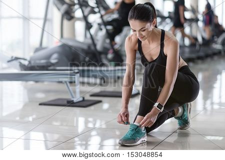 Important details. Delighted pretty young girl tying her shoelaces while wearing sneakers during the training.
