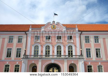 Facade of Estonian Parliament House with Estonian flag and big emblem in Toompea Castle.